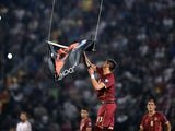 Serbia's defender Stefan Mitrovic grabs a flag with Albanian national symbols flown by a remotely operated drone during the UEFA Euro 2016 group F qualifying gootball match between Greece and Northern Ireland at the Karaiskaki stadium in Piraeus, near Ath