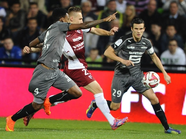 Metz' Belarussian midfielder Sergei Krivets (C) vies for the ball with Rennes' Mozambican defender Edson Mexer (L) and Rennes' French defender Romain Danze (R) during the French L1 match on October 18, 2014