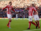 Stoke City's Scottish midfielder Charlie Adam celebrates scoring a penalty with teammate English-born Scottish defender Phil Bardsley (R) and English striker Peter Crouch (L) during the English Premier League football match between Stoke City and Swansea