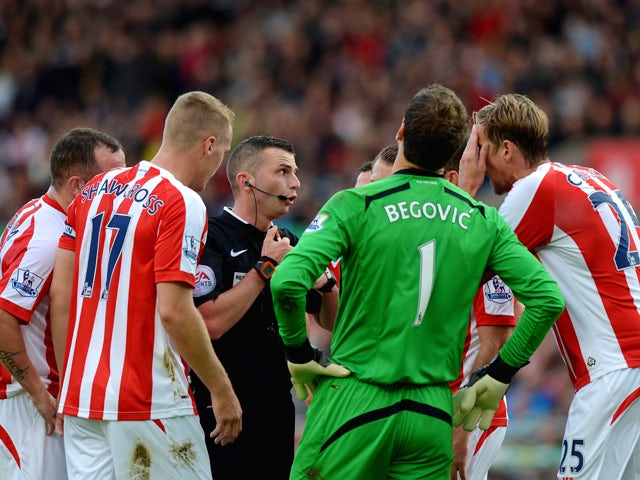 Stoke City players surround Referee Michael Oliver after he awarded Swansea City a penalty during the Barclays Premier League match between Stoke City and Swansea City at Britannia Stadium on October 19, 2014