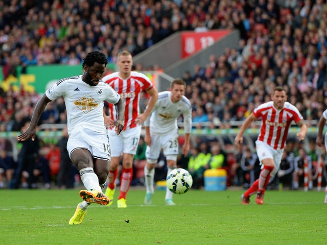 Wilfried Bony of Swansea City scores the first goal from the penalty spot during the Barclays Premier League match between Stoke City and Swansea City at Britannia Stadium on October 19, 2014