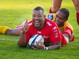 Toulon's flanker Steffon Armitage celebrates after scoring a try despite a tackle by Llanelli Scarlets' wing Michael Tagicakibau during the European Rugby Champions Cup match between Toulon and Llanelli Scarlets at the Mayol stadium in Toulon, southeaster