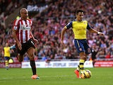 Alexis Sanchez of Arsenal outpaces Wes Brown of Sunderland to score the opening goal during the Barclays Premier League match between Sunderland and Arsenal at the Stadium of Light on October 25, 2014