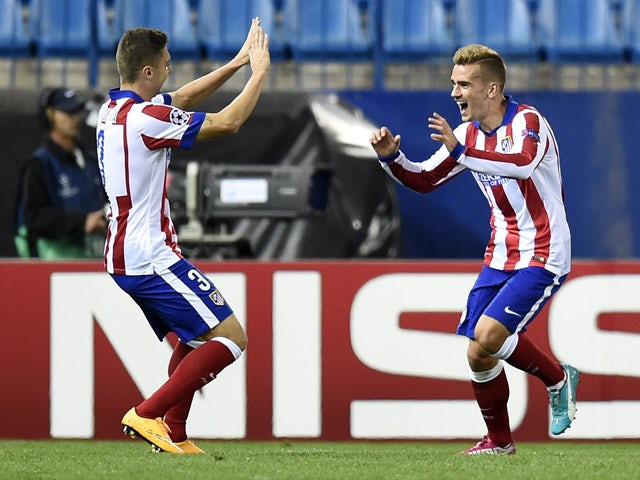 Atletico Madrid's French forward Antoine Griezmann celebrates with Atletico Madrid's Brazilian defender Guilherme Siqueira after scoring the third goal during the UEFA Champions League football match Club Atletico de Madrid vs Malmo FF at the Vicente Cald
