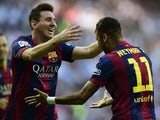 Barcelona's Brazilian forward Neymar celebrates wirh Barcelona's Argentinian forward Lionel Messi after scoring their first team goal during the Spanish league football match Real Madrid CF vs FC Barcelona at the Santiago Bernabeu stadium in Madrid on Oct