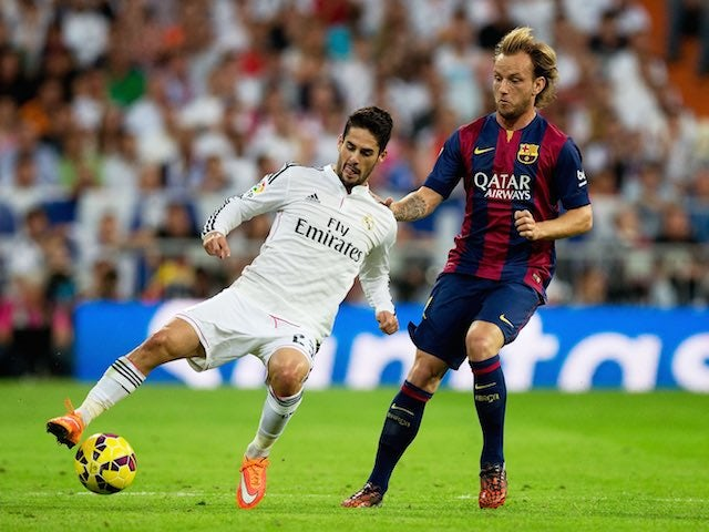 Real Madrid's Isco and Ivan Rakitic of Barcelona battle for the ball during el Clasico at the Bernabeu on October 25, 2014