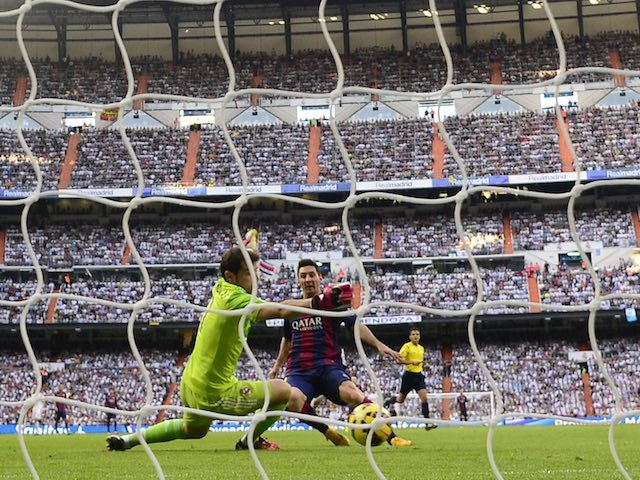 Iker Casillas intercepts as Lionel Messi takes a shot at goal during the El Clasico at the Bernabeu on October 25, 2014