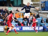 Lee Martin of Millwall jumps to head a ball under pressure from John Brayford of Cardiff during the Sky Bet Championship match between Millwall and Cardiff City at The Den on October 25, 2014