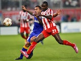 Olympiacos' Eric Abidal fights for the ball with Juventus' Carlos Tevez during the Group A Champions League football match Olympiacos vs Juventus at the Karaiskaki stadium in Athens' Piraeus district on October 22, 2014