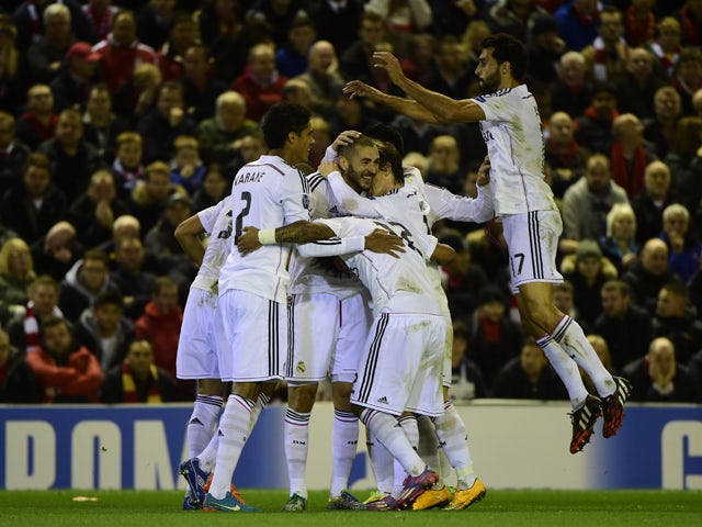 Real Madrid's Spanish defender Alvaro Arbeloa jumps on the press celebrating after Real Madrid's French forward Karim Benzema scored Real Madrid's third goal during the UEFA Champions League, group B, football match between Liverpool and Real Madrid at An