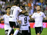 Valencia's players celebrate after scoring their third goal during the Spanish league football match Valencia FC vs Elche CF at the Mestalla stadium in Valencia on October 25, 2014