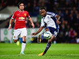Saido Berahino of West Bromwich Albion scores their second goal as Rafael of Manchester United looks on during the Barclays Premier League match between West Bromwich Albion and Manchester United at The Hawthorns on October 20, 2014