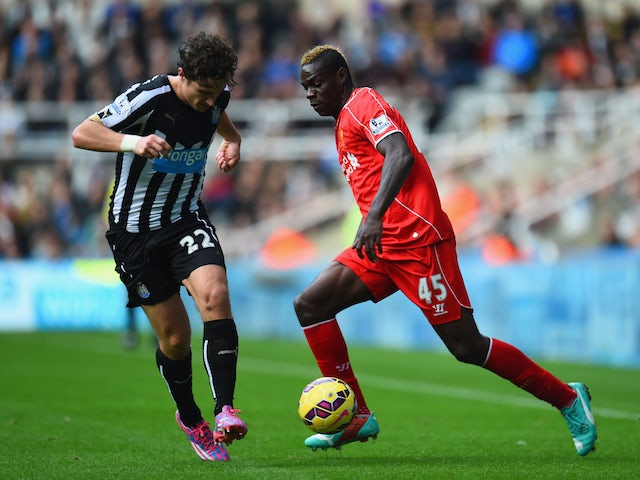 Daryl Janmaat of Newcastle United challenges Mario Balotelli of Liverpool during the Barclays Premier League match on November 1, 2014