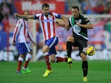 Gabi Fernandez of Club Atletico de Madrid battles for the ball against Lopez Garai of Cordoba CF during the La Liga match on November 1, 2014