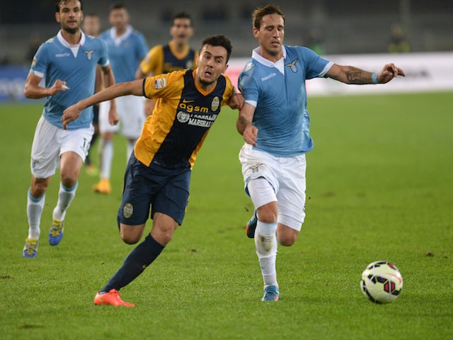 Gustavo Campanharo (L) of Verona competes with Lucas Biglia of Lazio during the Serie A match on October 30, 2014