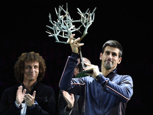Brazilian football player David Luiz applauds Serbia's Novak Djokovic (R) posing with his trophy after winning the final match against Canada's Milos Raonic at the Paris Masters Final on November 2, 2014