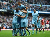 Sergio Aguero of Manchester City is mobbed by team mates after scoring the opening goal during the Barclays Premier League match against Manchester United on November 2, 2014
