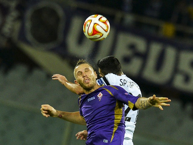 PAOK's defender Nikos Spyropoulos and Fiorentina's midfielder from Slovenia Jasmin Kurtic jump for the ball during theUEFA Europa League football match Fiorentina versus Paok, on November 6, 2014