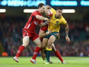 Israel Folau (R)of Australia is held up by George North (L) of Waes during the International match between Wales and Australia at the Millennium Stadium on November 8, 2014