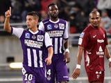 Toulouse's French Tunisian forward Wissam Ben Yedder celebrates after scoring a goal as Metz' French midfielder Florent Malouda looks on during the French L1 football match Toulouse vs Metz on November 8, 2014
