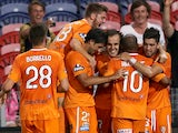 Roar players celebrate a goal during the round six A-League match between the Newcastle Jets and Brisbane Roar at Hunter Stadium on November 14, 2014
