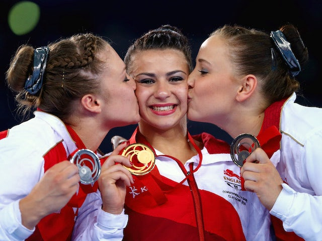 Claudia Fragapane of England is kissed on the podium by Ruby Harrold and Hannah Whelan after winning the Women's All-Around Final at the SECC Precinct during day seven of the Glasgow Commonwealth Games on July 30, 2014