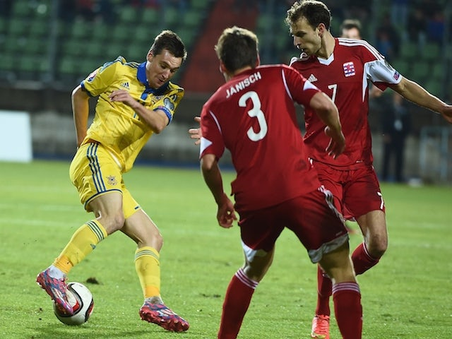 Ukraine's Denys Oliynyk vies with Luxembourg's Mathias Janisch (C) and Lars Gerson during the Group C Euro 2016 qualifying football match on November 15, 2014