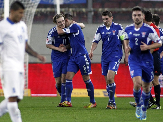 Faroe Island's Joan Edmundsson celebrates with his teammates after scoring a goal during the UEFA Euro 2016 group F qualifying football match between Greece and Faroe Island at the Karaiskaki stadium in Piraeus, near Athens, on November 14, 2014