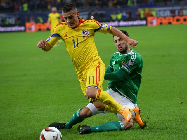 Romania's midfielder Gabriel Torje and Northern Ireland's defender Connor McLaughlin vie for the ball during the UEFA 2016 European Championship qualifying round Group F football match Romania vs Northern Ireland at the Arena Nationala stadium in Buchares