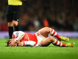 Jack Wilshere of Arsenal lies injured after a tackle during the Barclays Premier League match between Arsenal and Manchester United at Emirates Stadium on November 22, 2014