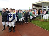 ockeys line up to observe a minutes silence after the death of former jockey and trainer Dessie Hughes at Cheltenham racecourse on November 16, 2014