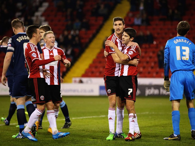 Chris Basham of Sheffield United congratulates Ryan Flynn on his goal during the FA Cup First Round Replay match between Sheffield United and Cewe Alexandra at Bramell Lane on November 18, 2014