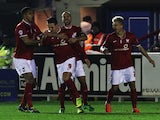 Wes Fletcher (#9) of York City is congratulated by team mates after opening the scoring during the FA Cup First Round Replay between AFC Wimbledon and York City at The Cherry Red Records Stadium on November 18, 2014
