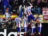 Atletico Madrid's players celebrate their first goal during the UEFA Champions League Group A football match Atletico Madrid vs Olympiakos FC at the Vicente Calderon stadium in Madrid November 26, 2014