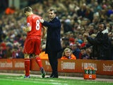 A fan applauds as Steven Gerrard of Liverpool prepares to come onto the pitch as a substitute alongside Brendan Rodgers manager of Liverpool during the Barclays Premier League match between Liverpool and Stoke City at Anfield on November 29, 2014