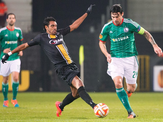 Lokeren's Sergio Junior Dutra and Legia's Ivica Vrdoljak fight for the ball during the UEFA Europa League Group L football match between KSC Lokeren OVL and Legia Warszawa on November 27, 2014