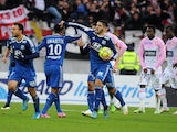 Lyon's French forward Yassine Benzia celebrates with teammates after scoring an equalizer during the French L1 football match Evian (ETGFC) against Lyon (OL) on December 7, 2014
