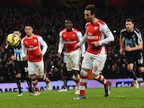 Arsenal's Spanish midfielder Santi Cazorla chips the ball as he scores their fourth goal from the penalty spot during the English Premier League football match between Arsenal and Newcastle United at the Emirates Stadium in London on December 13, 2014