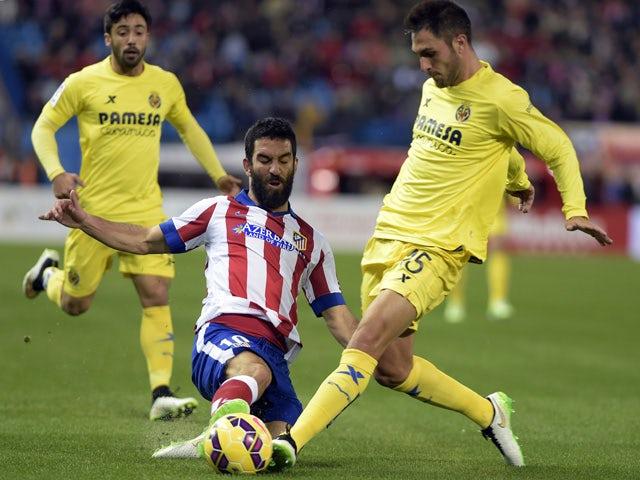 Atletico Madrid's Turkish midfielder Arda Turan vies with Villarreal's defender Victor Ruiz during the Spanish league football match Club Atletico de Madrid vs Villarreal CF at the Vicente Calderon stadium in Madrid on December 14, 2014