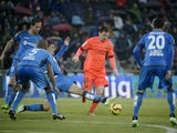 Getafe's Uruguayan defender Emiliano Velazquez vies with Barcelona's Argentinian forward Lionel Messi during the Spanish league football match Getafe CF vs FC Barcelona at the Col. Alfonso Perez stadium in Getafe on December 13, 2014