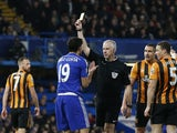 Referee Chris Foy shows Chelsea's Brazilian-born Spanish striker Diego Costa a yellow card for simulation during the English Premier League football match between Chelsea and Hull City at Stamford Bridge in London on December 13, 2014