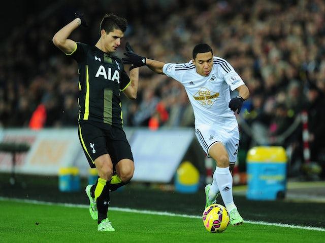 Spurs player Erik Lamela (l) challenges Swansea player Jefferson Montero during the Barclays Premier League match on December 14, 2014