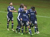 Evian's teammates celebrate after Evian's French midfielder Cedric Cambon celebrates after scoring a goal during the French L1 Football match Reims vs Evian, on December 13, 2014