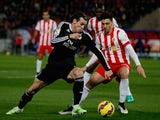 Gareth Bale (L) of Real Madrid CF competes for the ball with Joaquin Navarro JImenez (R) of Almeria UD during the La Liga match on December 12, 2014