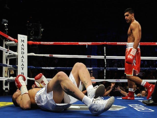 WBA super lightweight champion Amir Khan of England (R) looks at Marcos Maidana of Argentina on December 11, 2010