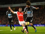 Mathieu Debuchy of Arsenal tackles Fabricio Coloccini of Newcastle United during the Barclays Premier League match on December 13, 2014