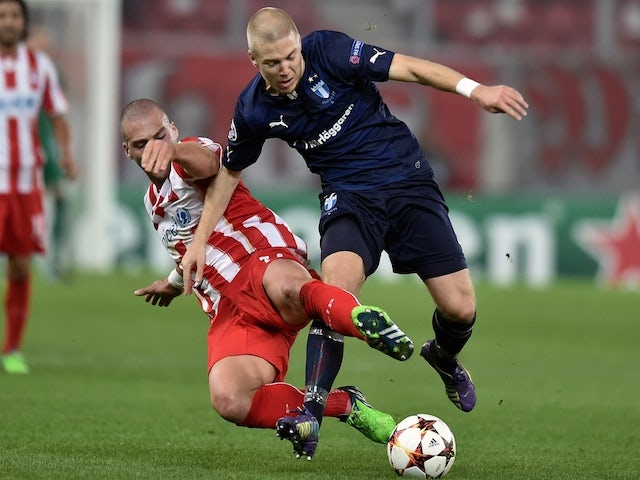 Olympiakos' Pajtim Kasami (L) fights for the ball with Malmo's defender Anton Tinnerholm (R) during the UEFA Champions League Group A football match on December 9, 2014