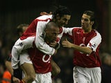 Arsenal's Robert Pires (top) and Mathieu Flamini (R) congratulate Thierry Henry after he scored the opening goal against Chelsea during the Premiership match on December 12, 2004