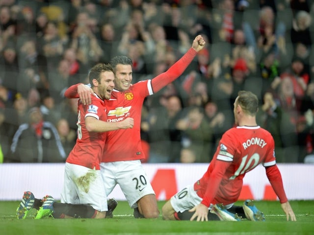 Manchester United's Dutch striker Robin van Persie (2nd L) celebrates scoring their third goal with Juan Mata and Wayne Rooney during the game with Liverpool on December 14, 2014