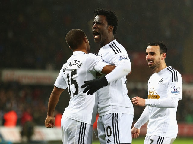 Wilfried Bony of Swansea City celebrates his goal with Wayne Routledge (L) and Leon Britton during the Barclays Premier League match between Swansea City and Tottenham Hotspur at Liberty Stadium on December 14, 2014
